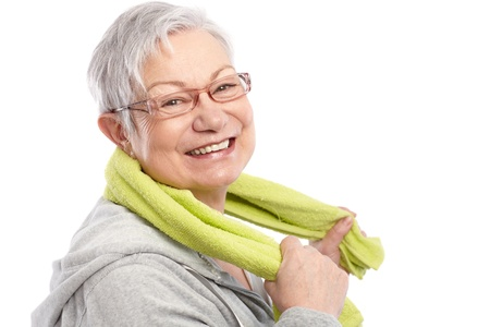 Energetic old woman smiling after workout, holding towel around neck 65533;