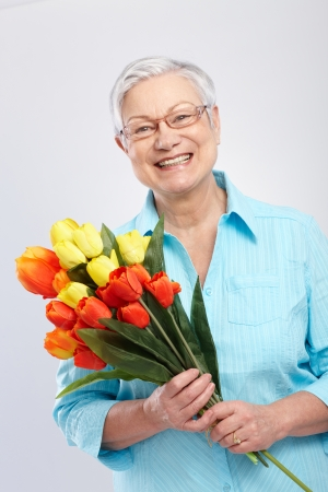 60s adult: Grandmother holding bouquet of flowers, smiling   65533;