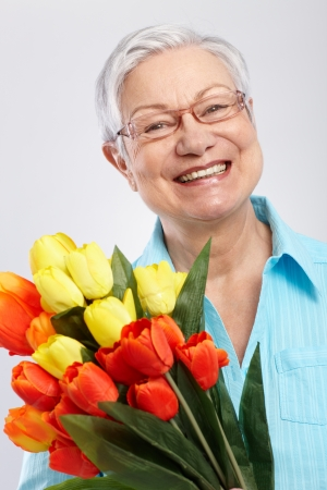 mothering: Portrait of elderly lady with bouquet of fresh tulips, smiling   65533; Stock Photo