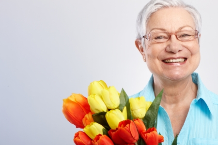 mothering: Happy grandmother holding bouquet of tulips at mother