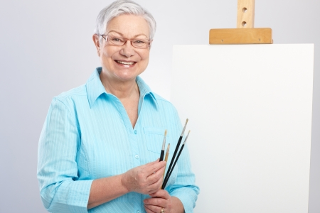 Happy old lady as hobby painter with canvas and paintbrush   65533; photo