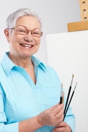 caritas pintadas: Mujer de edad activa con pincel y el lienzo, sonriente 65533; Foto de archivo