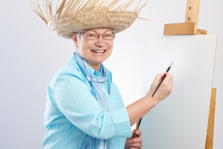 Old lady painting on canvas by paintbrush, smiling   65533; photo