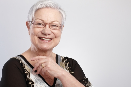 Closeup portrait of smiling elderly lady in glasses   65533; photo