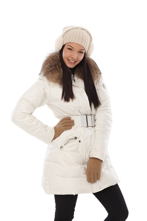 Happy young woman posing in white winter coat   65533; photo