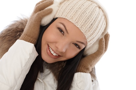 earmuffs: Winter portrait of smiling young woman in white cap and earmuffs   65533;