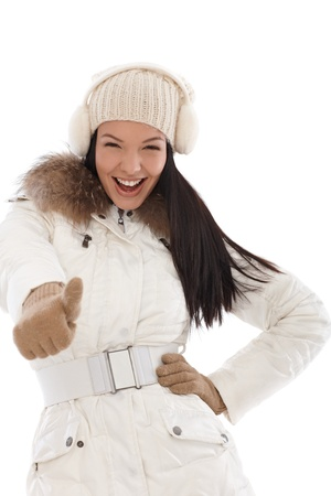 earmuffs: Cool woman smiling with thumb up at wintertime wearing white coat and knitted cap   65533;