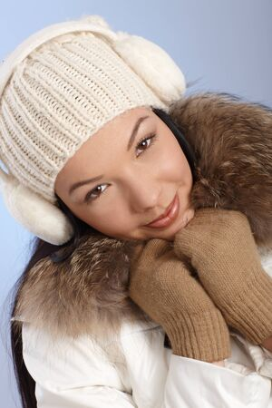 Attractive young female at winter in white cap and coat and earmuffs   65533; Stock Photo - 13944844