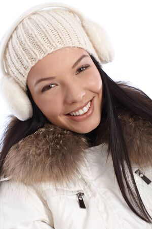 earmuffs: Closeup portrait of smiling young woman dressed up warm at wintertime.