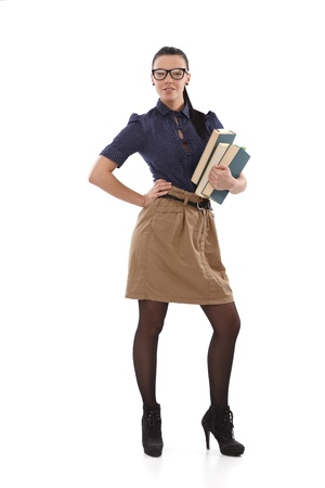 short skirt: Stylish young schoolmistress posing with books in hand, other hand on hip.