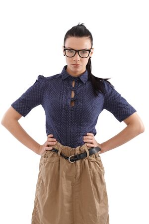strict: Strict school-marm standing hands on hip, looking at camera, wearing glasses. Stock Photo