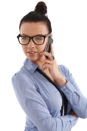 Attractive young businesswoman talking on mobile phone, wearing bun and glasses. photo