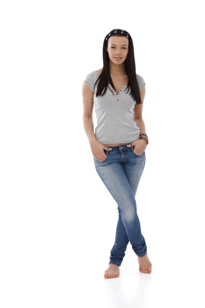 Young student standing in jeans and t-shirt barefoot, hands in pocket. photo