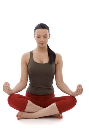 Young girl practicing yoga, sitting in tailor seat, relaxing eyes closed. Stock Photo - 13926828