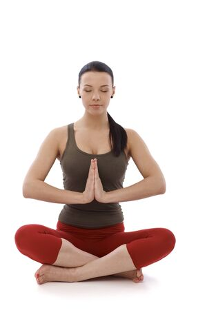 Young woman practicing yoga, meditating in prayer position eyes closed. photo