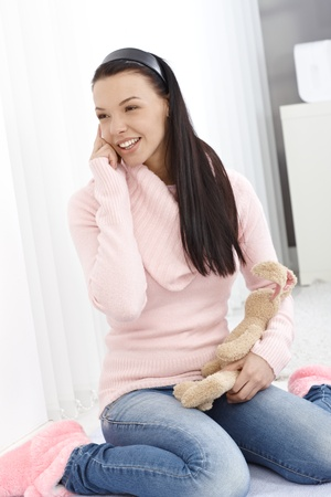 Happy girl sitting on floor at home, holding soft toy in hand, talking on mobile phone. photo
