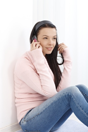 Young attractive woman sitting on floor at home, talking on mobile phone, looking away. photo