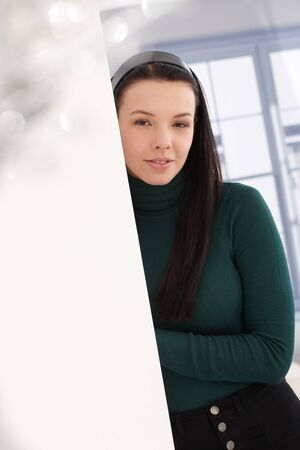 woman sweater: Portrait of attractive young female leaning to wall, looking at camera.