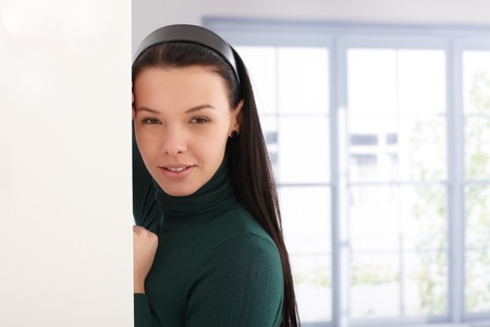 Portrait of beautiful girl leaning to wall, smiling by window. Stock Photo - 13927038