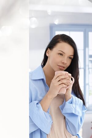 Young attractive woman drinking morning tea, smiling, looking away, through window. photo