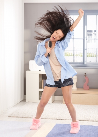 Happy young woman acting as pop star, using hairbrush as microphone, wearing pyjamas, long hair flying in the air. Stock Photo - 13927044