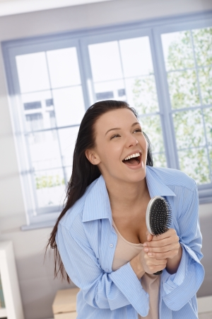 Happy woman acting as pop star, singing to hairbrush as microphone, laughing, having fun. photo