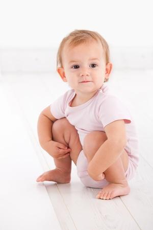 squat: Cute baby girl crouching on floor in pink short sleeve bodysuit   65533;