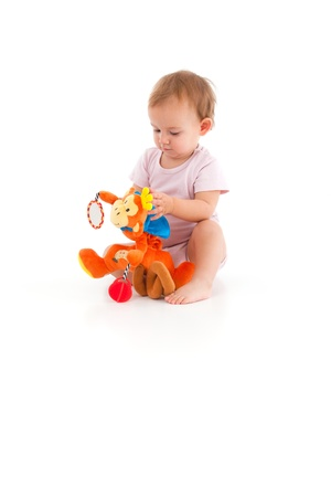 soft toy: Baby girl in pink bodysuit playing with soft toy