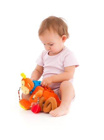 Cute baby girl lost in playing with soft toy   Stock Photo