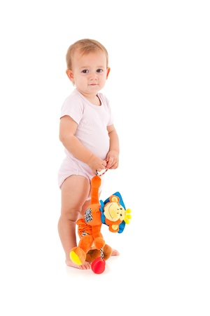 Little girl holding soft toy monkey in hand, standing, looking at camera  photo
