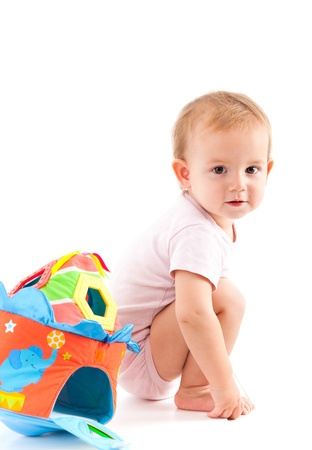 cute baby girl: Cute baby girl squatting on floor, having toys