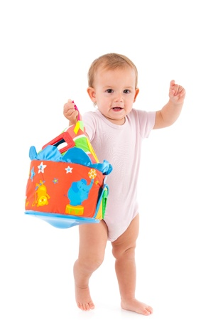 bodysuit: Lovely toddler girl holding toy in hand, standing, concentrating   Stock Photo