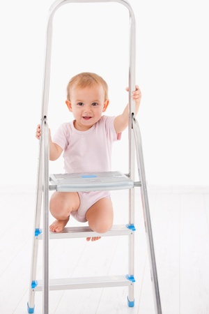 Cute baby girl climbing on ladder, smiling   Stock Photo