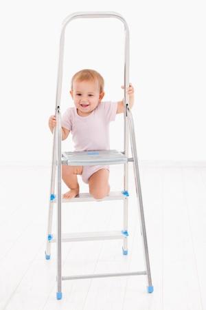 impish: Adorable baby girl in bodysuit climbing on ladder, smiling   Stock Photo