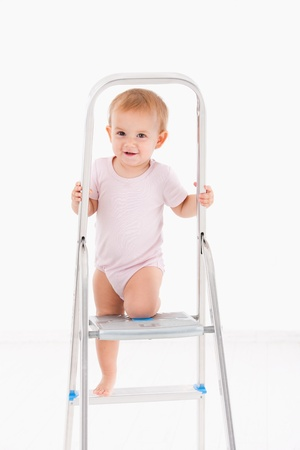 image size: Cute baby girl climbing on ladder wearing bodysuit  Stock Photo