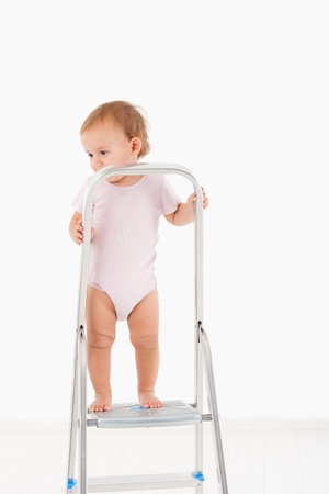 Toddler in bodysuit standing on top of ladder photo
