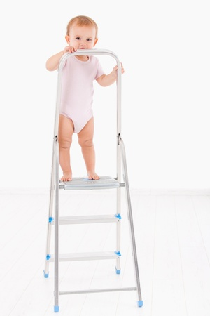 Lovely baby girl in short sleeve bodysuit standing on top of ladder, smiling  photo