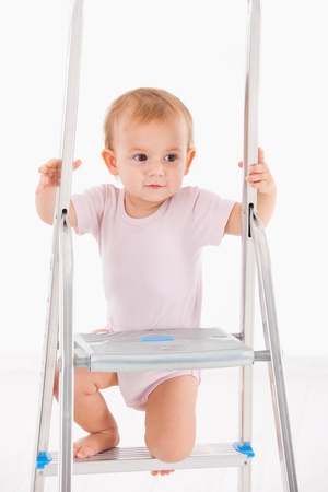 Beautiful baby girl in bodysuit climbing on ladder  photo