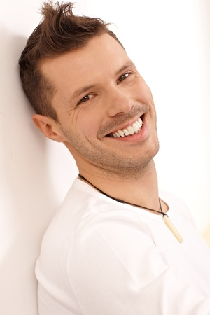 bristly: Portrait of happy young man leaning to wall, smiling, looking at camera. Stock Photo