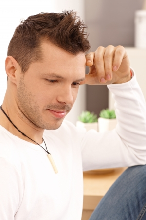 Young man thinking at home, looking down. Stock Photo - 13961792
