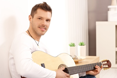 Portrait of young goodlooking guitarist, playing guitar at home. Stock Photo - 13964673