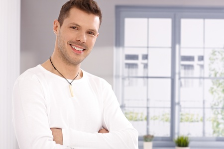 Portrait of handsome young man standing arms crossed by window, smiling. Stock Photo - 13964676