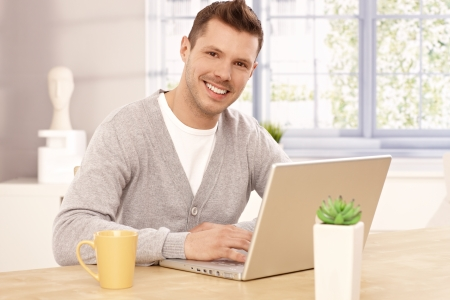 young unshaven: Handsome young man browsing internet at home, smiling, looking at camera.