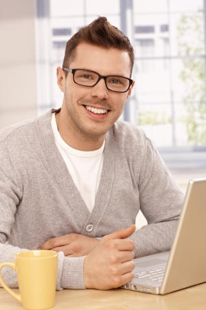 Handsome guy in glasses using laptop computer at home, smiling. photo