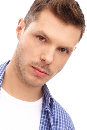 Closeup portrait of serious young man with trendy hairstyle. photo