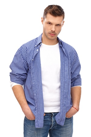 Serious looking young man standing with hands in pockets. photo