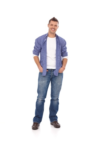 full size: Happy young guy standing with hands in pockets. Stock Photo
