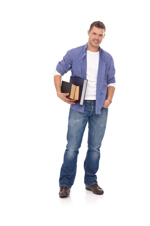 Casual student holding books, smiling. Full size. Stock Photo - 13964637