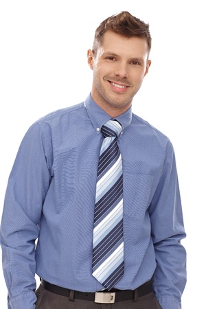 Portrait of confident businessman standing with hands in pockets, smiling. photo