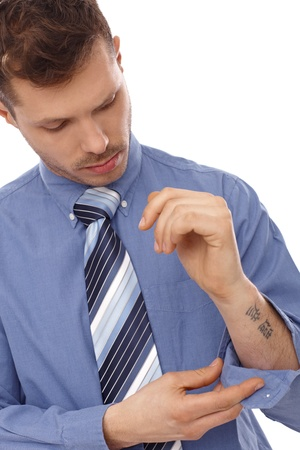 forearm: Young businessman in blue shirt with tattoo in forearm.
